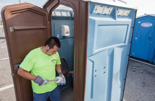 Andrew Caprioni replenishes paper supplies in porta potty